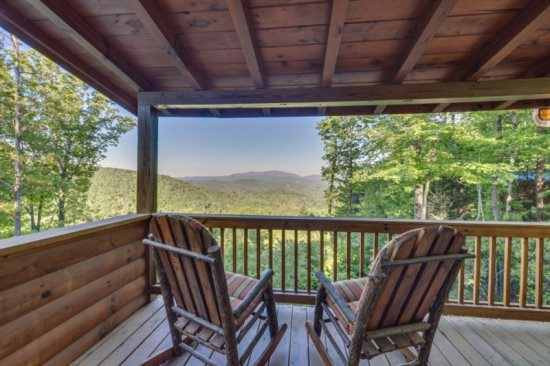 Above it all rental cabin deck with two chairs overlooking the mountains